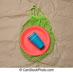stack of blue paper cups and red round plates on a brown paper background