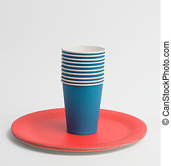 stack of blue paper cups and red round plates on a white background