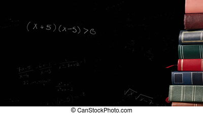 Stack of books against mathematical equations on black board...