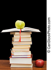 Stack of books and apple On a black background