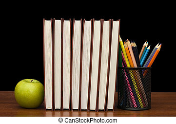 Stack of books and apple on a wooden table