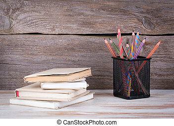 Stack of books and pencils on the wooden table