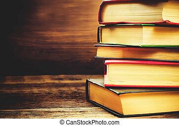 stack of books on the dark wood background. toning....