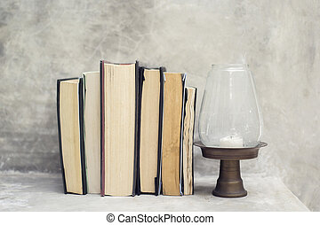 stack of books on the shelf and near the lamp