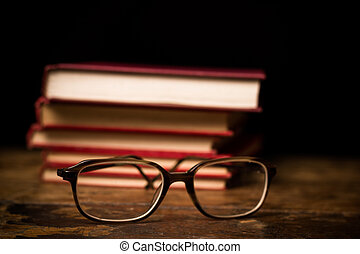 Stack of books with a pair of glasses
