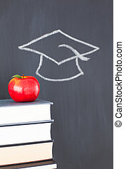 Stack of books with a red apple and a blackboard with a graduation cap drawn on it
