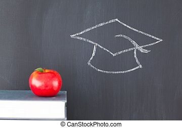 Stack of books with a red apple and a blackboard with a...