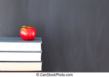Stack of books with a red apple and a clean blackboard