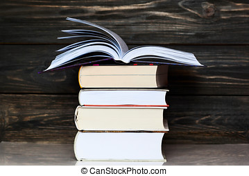 Stack of books with dark wooden background. One book is opened