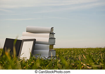 Stack of books with ebook reader outdoors laying on grass