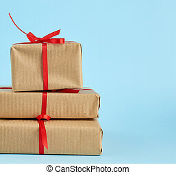 stack of boxes wrapped in brown paper and tied with a red bow