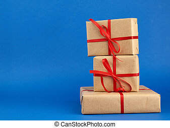 stack of boxes wrapped in brown paper and tied with a red bow, gifts on a blue background
