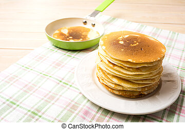 Stack of breakfast pancakes on the white plate and green pan