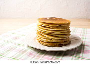 Stack of breakfast pancakes on the white plate