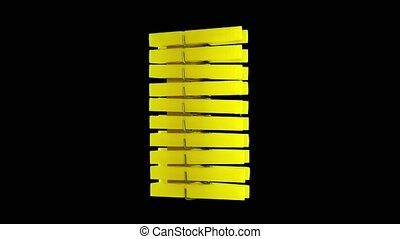 Large stack of new bright yellow plastic clothespins as stylish household tools turns slowly on black background close view