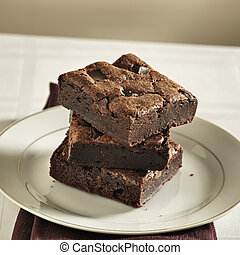 Stack of brownies on a plate.