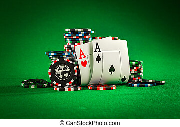 Stack of chips and two aces on the table on the green baize