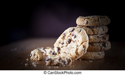 Stack of chocolate chip cookies on wooden table. Shallow DOF. Fo