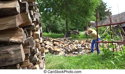 Stack of chopped wood and blurred farmer man prepare firewood in yard. 4K