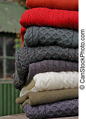 Stack of chunky Irish wool cable knit and Aran winter sweaters in fall and winter colours in a pretty Irish rural setting.