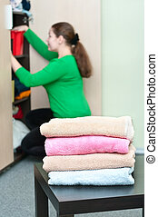 Stack of clothes and young caucasian woman arranging things...