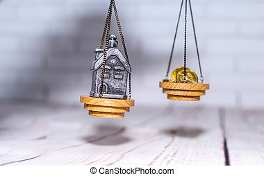 Stack of coins and a small house on the scales. The concept of choice, cash savings and purchase of real estate.