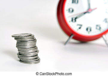 Stack of coins and alarm clock