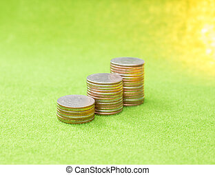 Stack of coins on green background