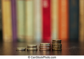 stack of coins on the background of books