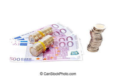 Stack of coins over a euro bills