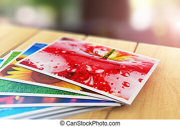 Stack of color photo pictures on wooden table outdoors