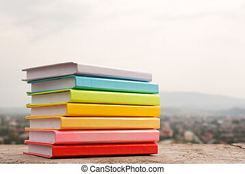 Stack of colorful books laying outdoors