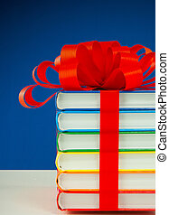 Stack of colorful books tied up with red ribbon