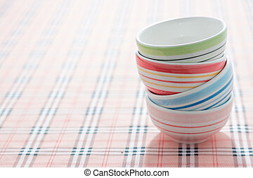 stack of colorful bowls on fabric background