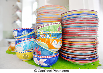 stack of colorful hand painted ceramic bowls and plates