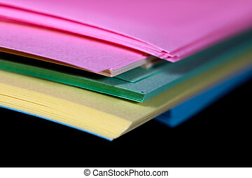 Stack of colorful papers on black background