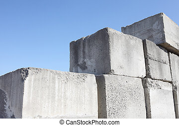 stack of concrete blocks, construction site against a blue...