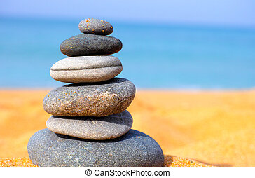 Stack of dark stones on sea beach