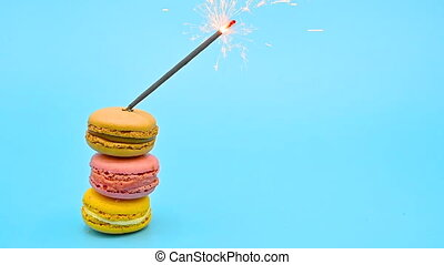 Stack of delicious macaron with burning sparkle on blue pastel background. Celebrating concept .