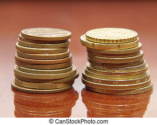 Stack of different coins on a polished table.