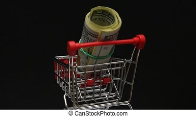 Stack of dollars rotating in trolley from supermarket. Money in shopping trolley cart. Online shopping. Commerce.