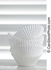 Stack of Empty Cupcake Cases over White Slat Background