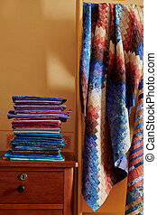 Stack of fabrics and quilt made in the bargello style on yellow wall background