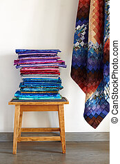 Stack of fabrics on a stool and quilt top made in the bargello style on neutral wall background