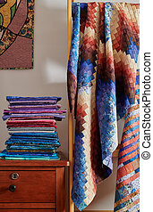 Stack of fabri?s and quilt made in the bargello style on white wall background