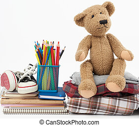 stack of folded clothes, sports sneakers, stationery and a brown teddy bear on a white background