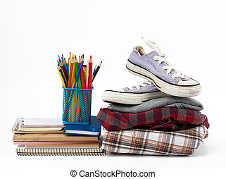 stack of folded clothes, sports sneakers, stationery on a white background