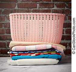 stack of folded laundry and empty laundry basket, brown brick wall background