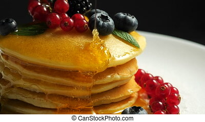 Stack of fresh fluffy pancakes decorated on top with forest berries rotating on plate and pouring honey syrup. Delicious, healthy american breakfast. Fresh bakery concept. 4k.