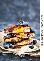 Stack of freshly prepared blueberry ricotta pancakes with...
